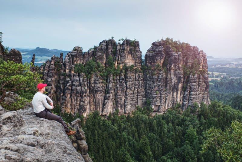 岩石边缘的旅客人与在背景的锋利的岩石 免版税库存图片