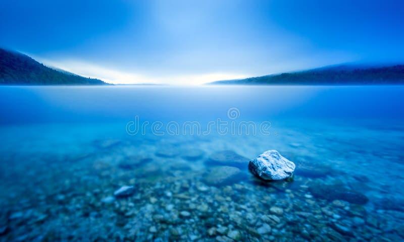 岩石长的曝光在Pebble海滩的湖蓝色早晨光的 库存图片