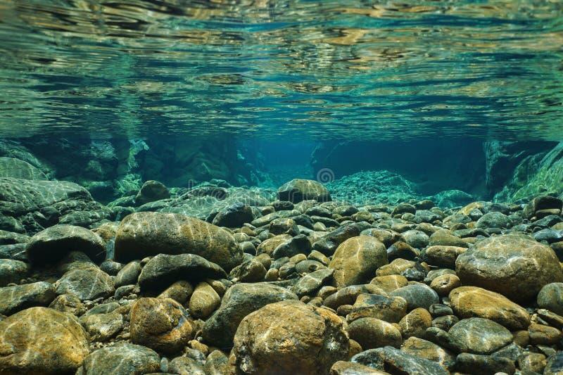 岩石水下在与清楚淡水的河床 免版税库存图片