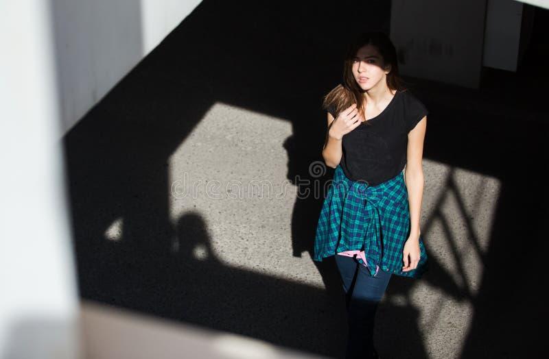 岩石黑色样式的深色的女孩,站立户外在城市街道 免版税库存图片