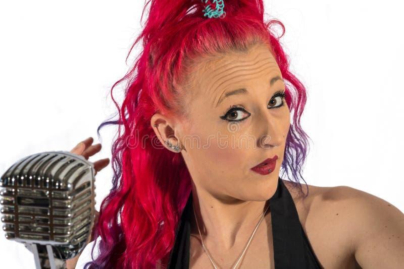 岩石` n `有红色头发和话筒的卷歌手 图库摄影