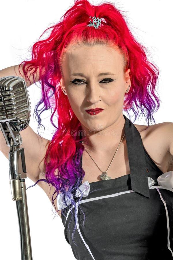 岩石` n `有红色头发和话筒的卷歌手 库存图片