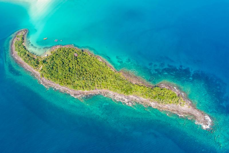 岩质岛海海滩有绿色树鸟瞰图 库存照片