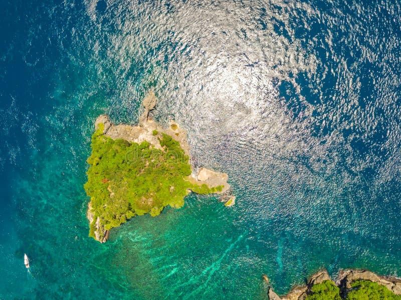 岩质岛长满与密林和小船 鸟瞰图 免版税图库摄影