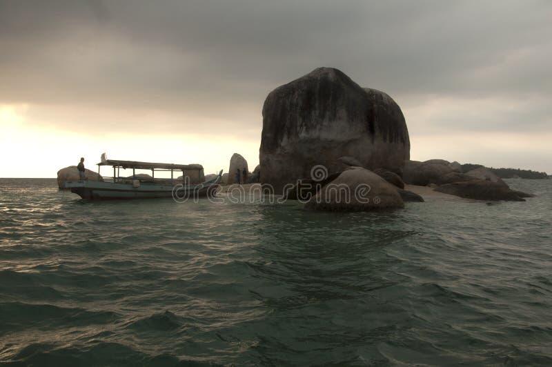 岩质岛和渔夫小船 库存图片