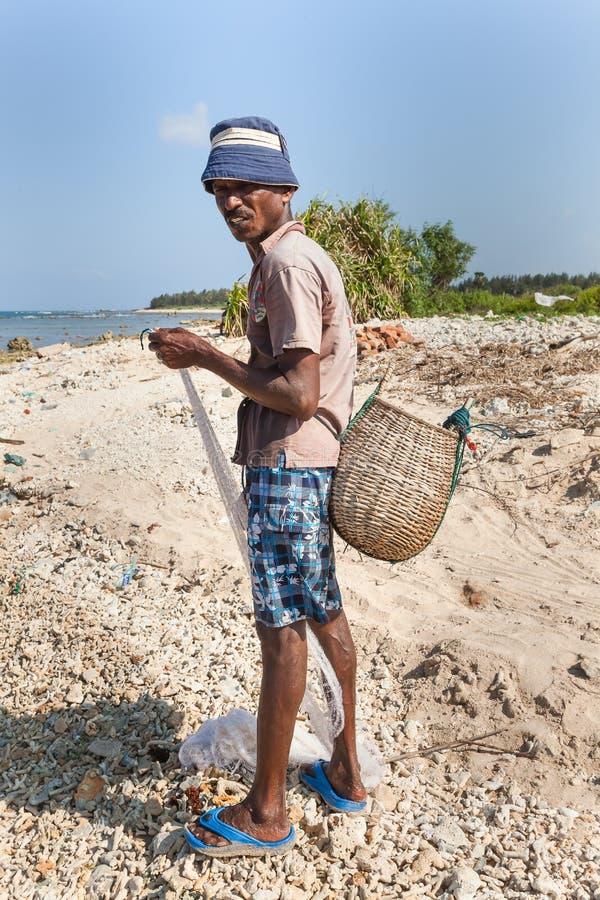岸的亚洲渔夫与鱼篮子在他的shoulde的 图库摄影
