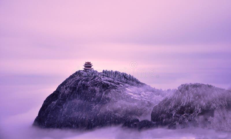 峨眉山` s精神道路是长和远的,云彩山在金黄寺庙光亮的金黄光的雾盖子 库存图片