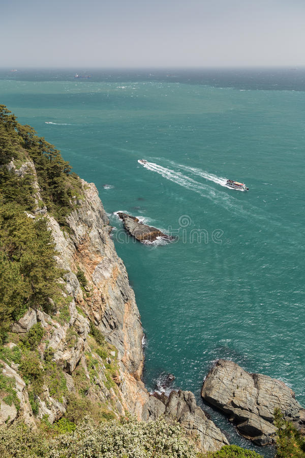 峭壁、海洋和从上面被观看的汽艇 免版税库存照片