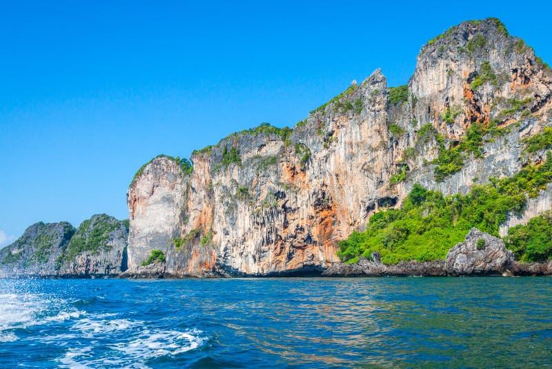 峭壁和清楚的海有一条小船的在发埃发埃海岛附近南部的 库存照片