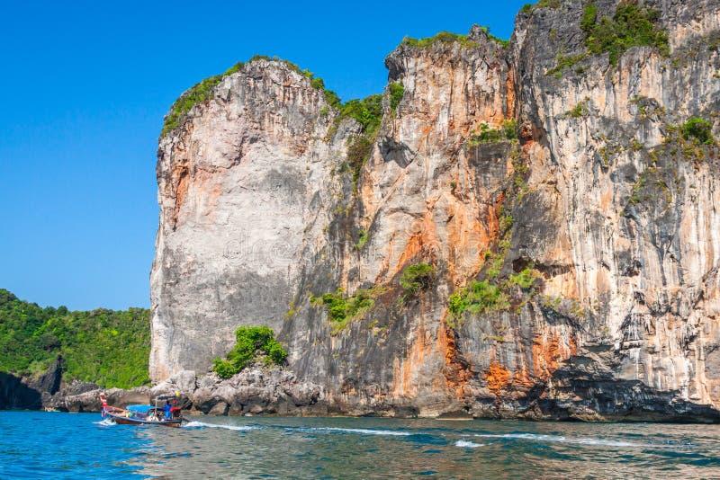 峭壁和清楚的海有一条小船的在发埃发埃海岛附近南部的 免版税库存照片