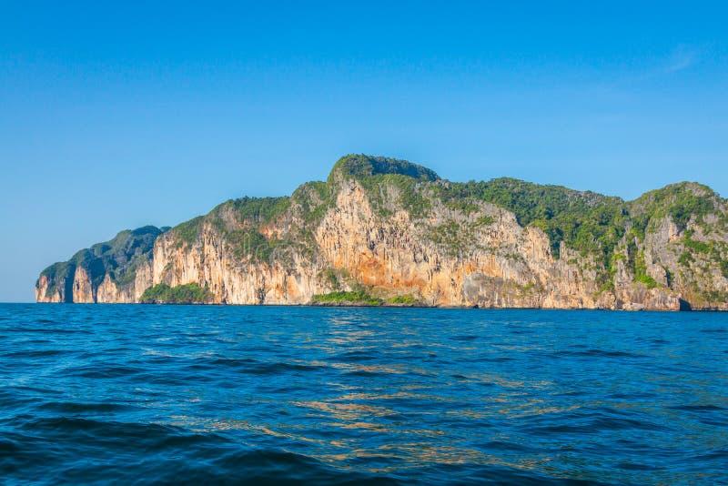峭壁和清楚的海有一条小船的在发埃发埃海岛附近南部的 免版税图库摄影