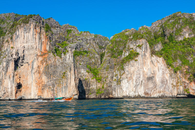 峭壁和清楚的海有一条小船的在发埃发埃海岛附近南部的 图库摄影