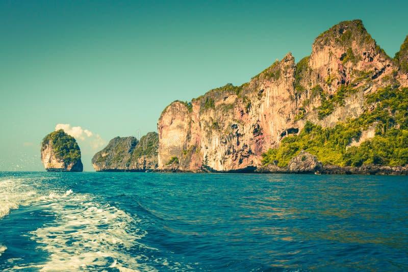 峭壁和清楚的海有一条小船的在发埃发埃海岛附近泰国的南部的 库存照片
