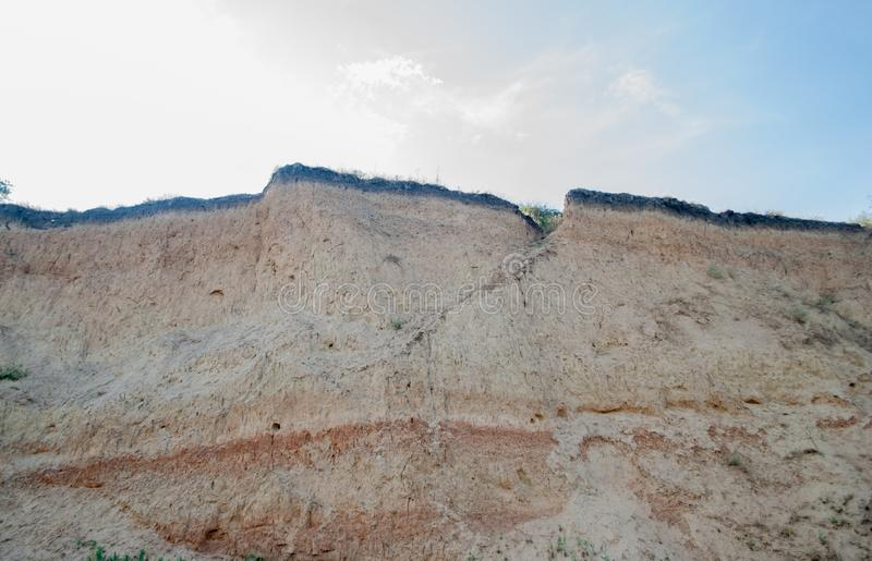 峭壁土壤层数是可看见的地方,以上它天空和云彩 库存照片