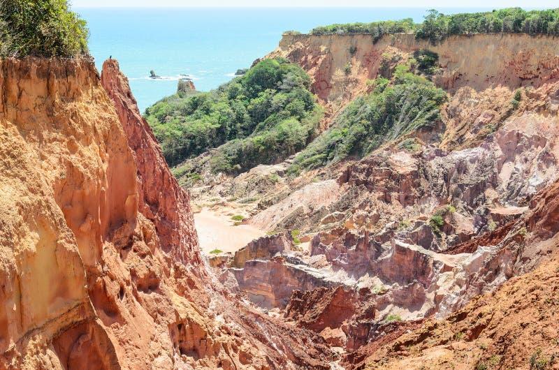 峭壁峡谷与许多石头的在时间之前沉淀了、岩石与红色和黄色颜色和海在背景中 免版税图库摄影