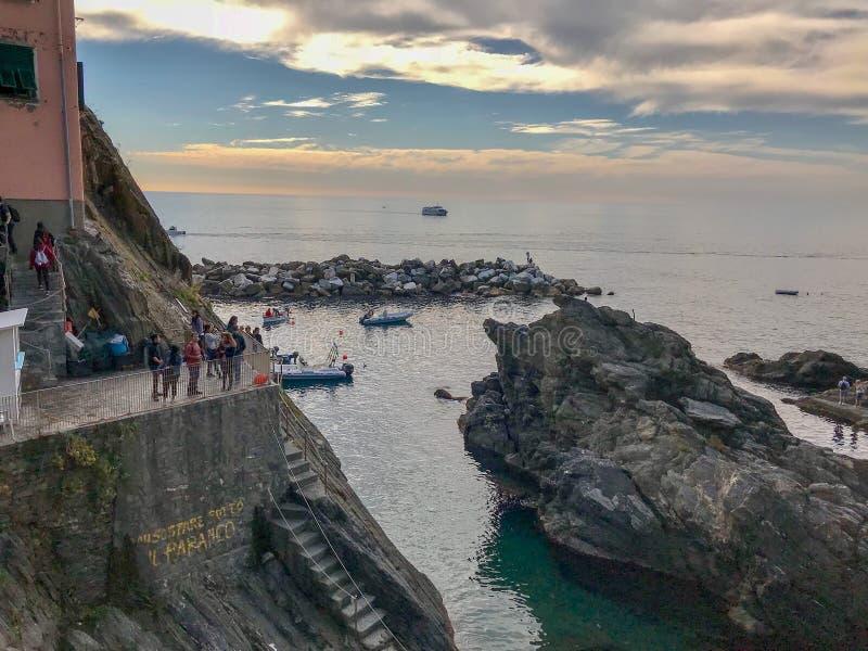 峭壁步行和小船的访客在里奥马焦雷的海, 库存图片