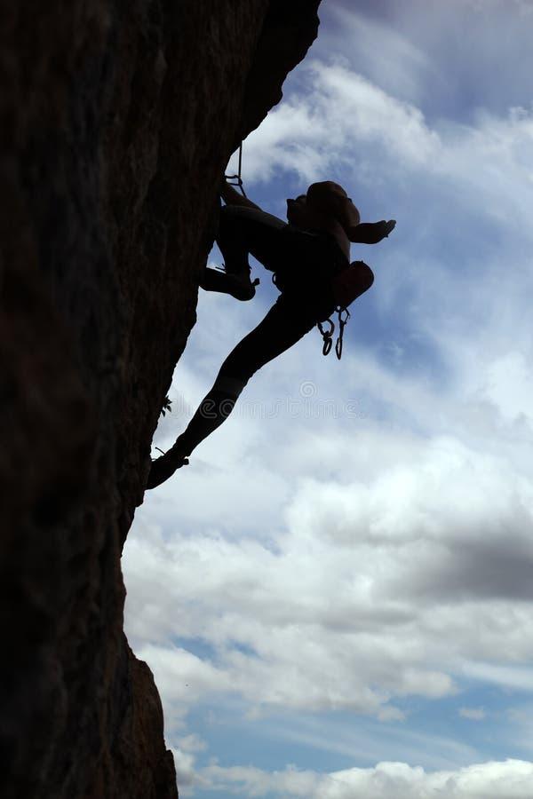 峭壁登山人上升的岩石剪影 图库摄影