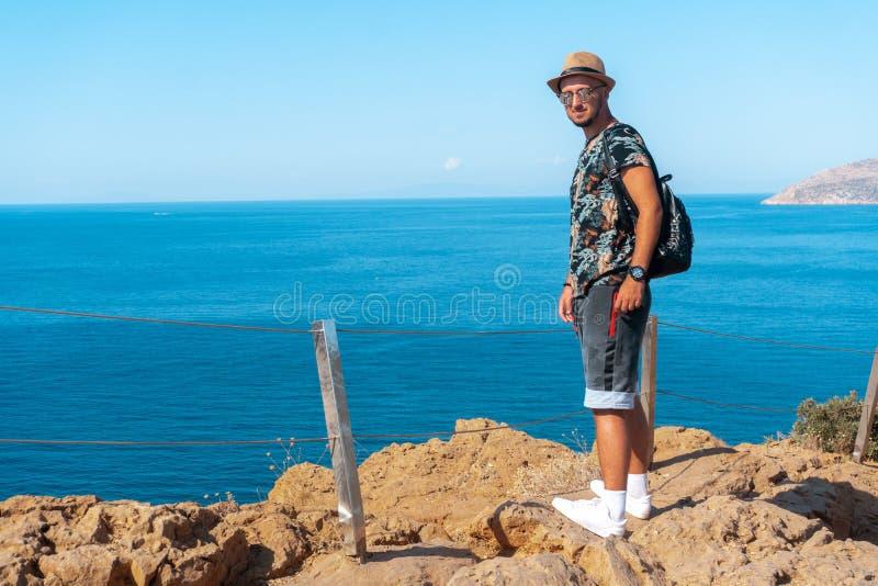 峭壁的时髦的年轻人由海 免版税库存照片