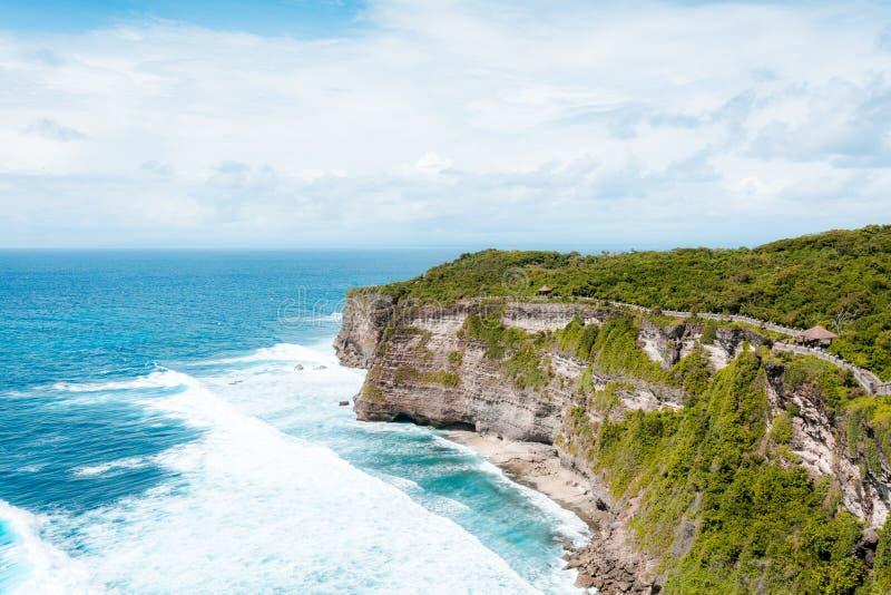 峭壁的看法与波浪的在从印度寺庙Pura Luhur Uluwatu的海 免版税库存照片