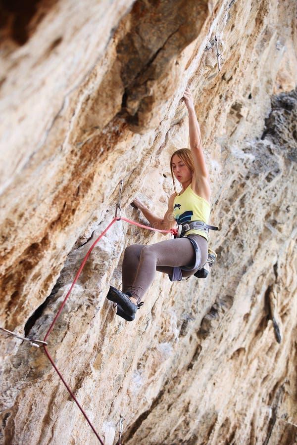 峭壁的年轻女性攀岩运动员 免版税库存照片