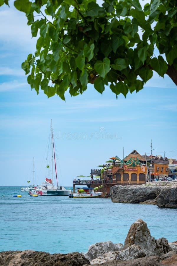 峭壁边在加勒比岛上的绿松石海洋 享受晴朗的夏日的游人在蒙特奇湾牙买加 库存图片