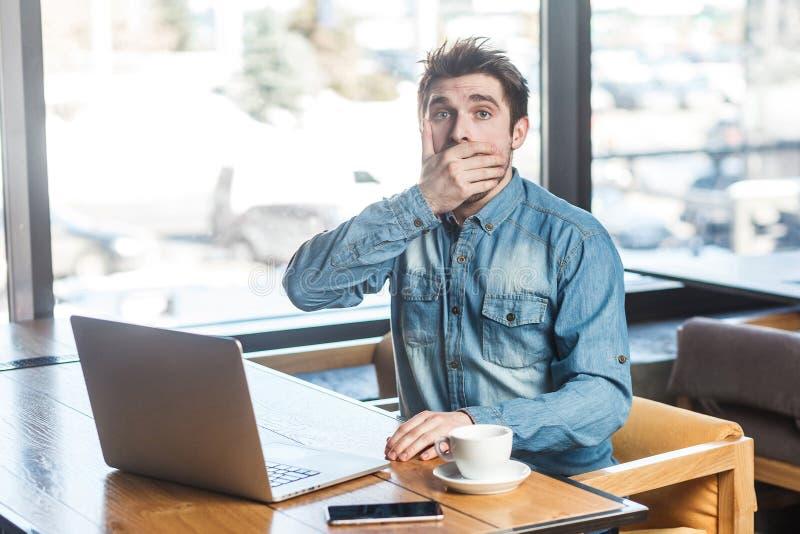 崩溃!情感害怕的年轻商人侧视图画象在蓝色牛仔裤衬衣的在咖啡馆坐并且盖嘴 免版税库存图片