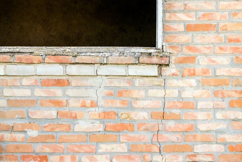 崩裂在砖墙在一个窗口下在一个空的房子里 破裂 免版税库存照片