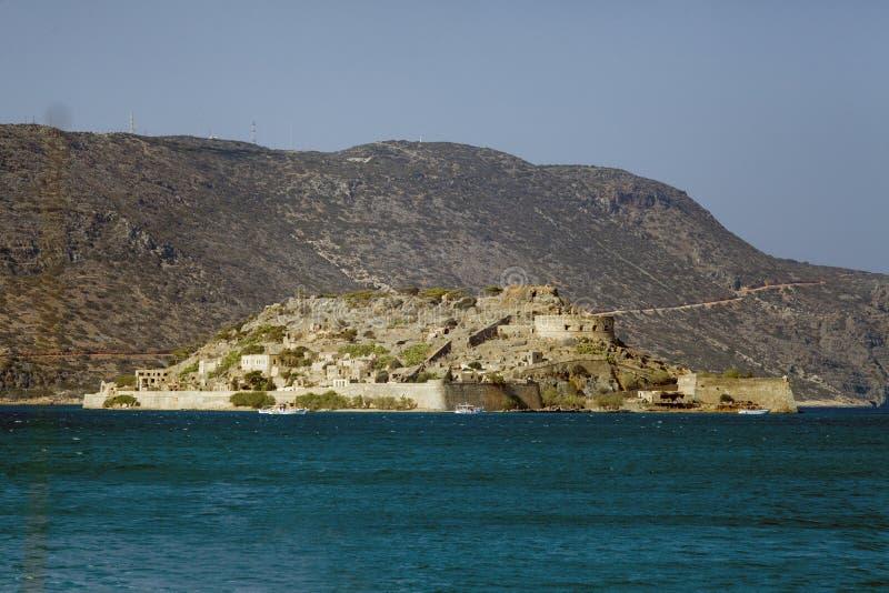 巡航到史宾纳隆加岛海岛  在蓝色盐水湖的小船 在克利特,希腊海岛上的史宾纳隆加岛堡垒  库存图片