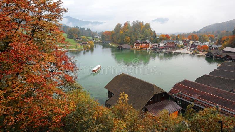 巡航在Konigssee (King's Lake)的一条观光的小船围拢由五颜六色的秋天树和船库 库存图片