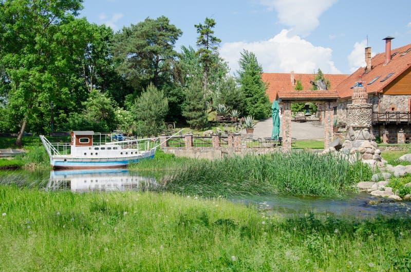 巡航小舟摆渡船停泊了在码头靠近古老庄园 免版税库存照片