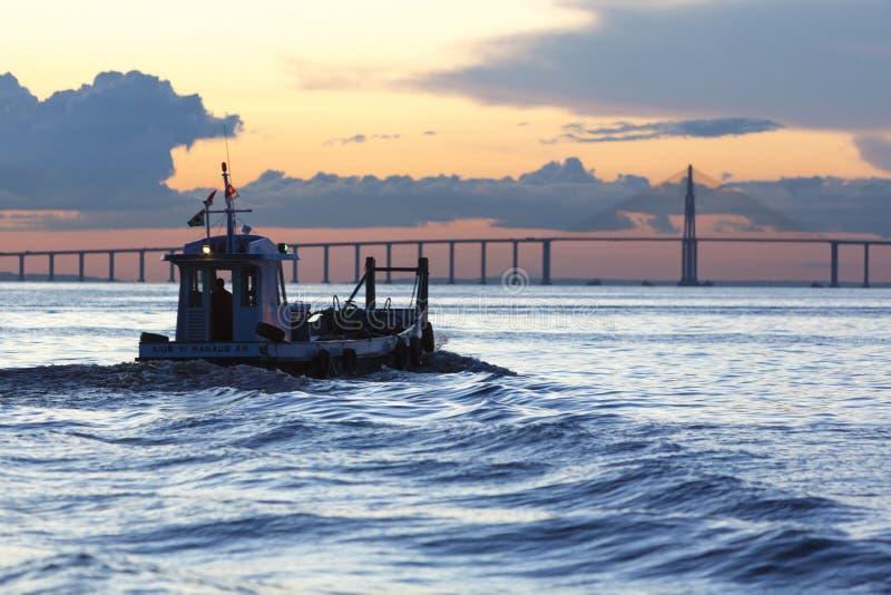 巡航小船的日落和的剪影亚马孙河,巴西 免版税图库摄影