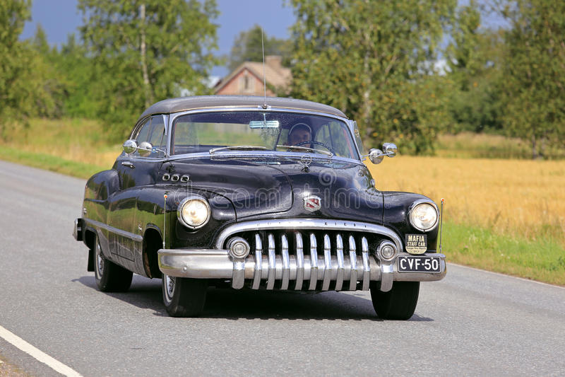 巡航沿农村路的黑别克超级八经典之作汽车 免版税库存照片