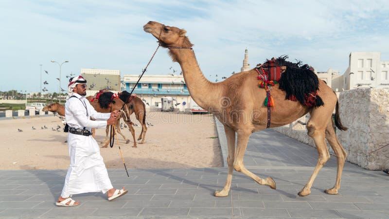 巡逻游人Souk Waqif与骆驼的Qatari警察 免版税库存图片