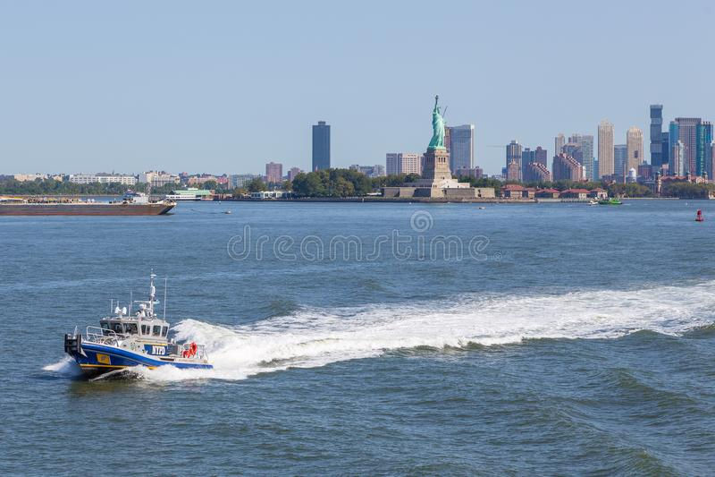 巡逻East河的NYPD小船 在背景自由女神像和摩天大楼新泽西中 免版税库存图片