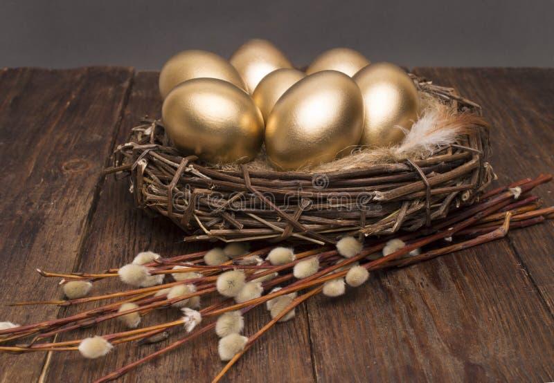 巢用与杨柳的金黄鸡蛋在木背景 复活节 免版税库存图片