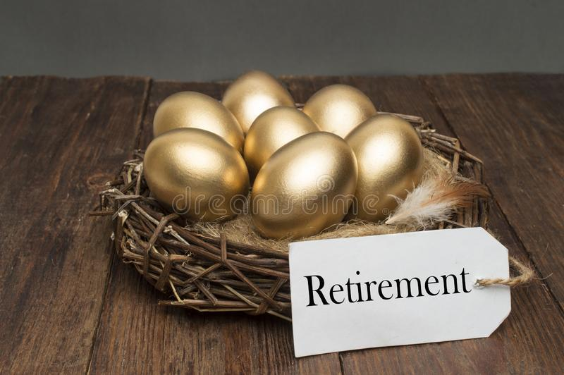 巢用与标记的金黄鸡蛋和在木背景的词退休 成功的退休的概念 库存照片