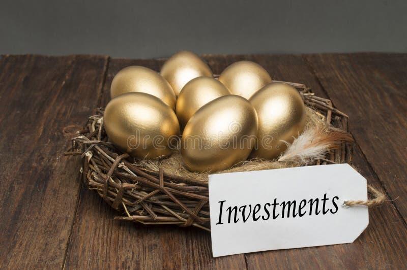 巢用与标记的金黄鸡蛋和投资的词在木背景的 成功的退休的概念 免版税库存照片
