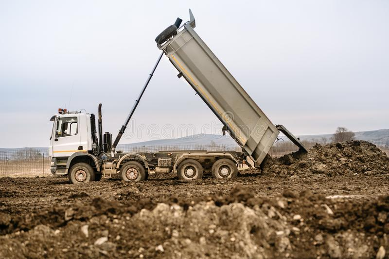 工业倾销者卡车联合国装货石渣和地球在高速公路建造场所 库存图片