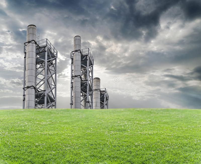 工业区和钢管道与绿色草坪和剧烈的天空 免版税库存图片