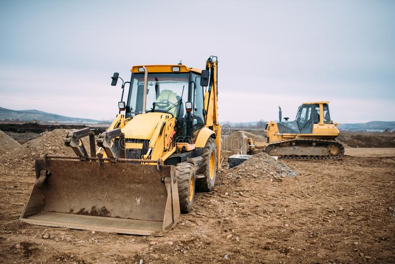 工业反向铲挖掘机装载者和推土机机械在建造场所 免版税库存照片