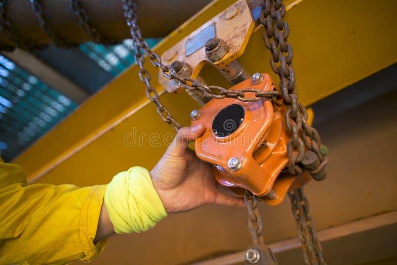 工业在举的卷扬机起重机的绳索通入审查员工作者装配工人手开始的安全每日检查检查 库存图片