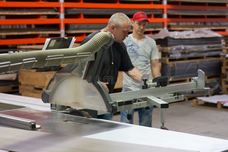 工业在木门家具制造业期间的木匠工作者运行的木切割机 库存图片