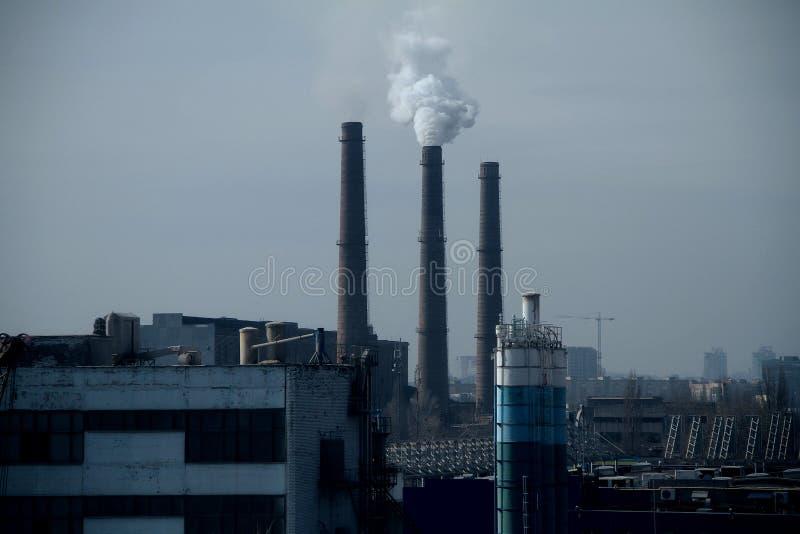 工业工厂污染空气烟窗在烟雾下的在天空 免版税库存照片