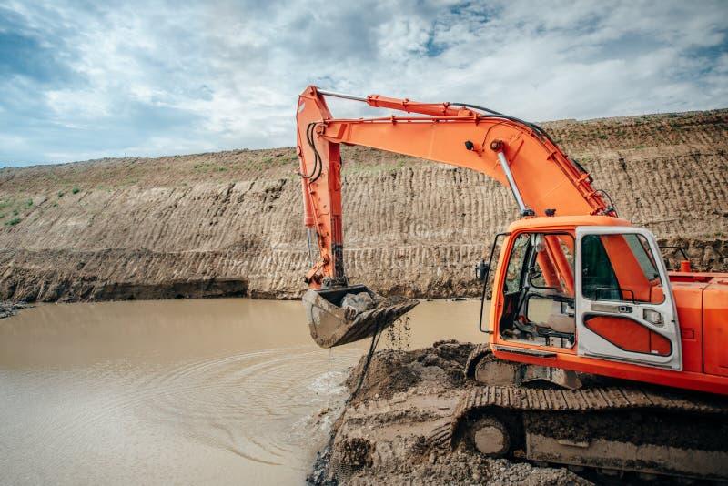 工业工程师与挖掘机一起使用在高速公路建造场所期间、装载的倾销者卡车和修造的高架桥和桥梁 免版税图库摄影