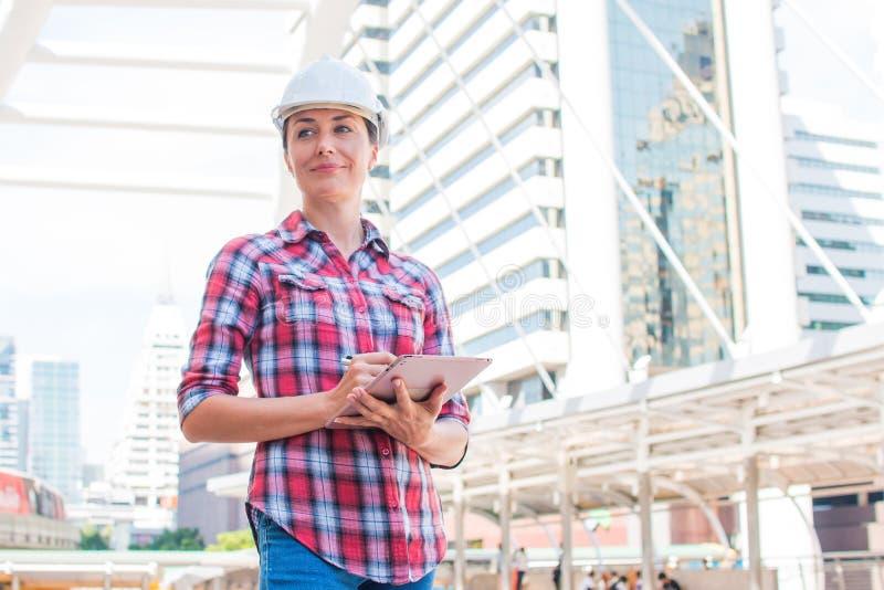 工业建筑工程师佩带安全帽工程学工作和在大厦外部的数字片剂 库存照片