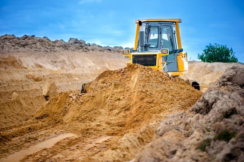 工业推土机和挖掘机与在sandpit的地球一起使用 库存图片