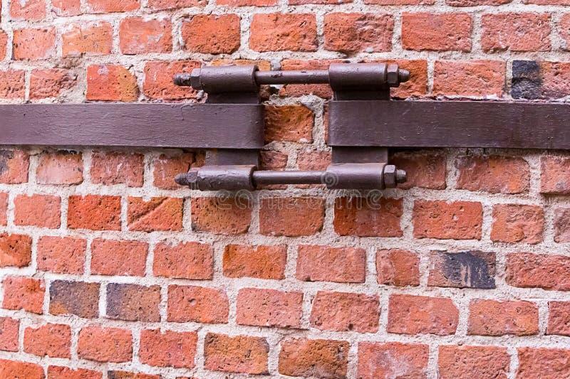 工业管子的背景紧固的破裂的墙壁生锈的老紧固紧固了红砖墙壁 免版税库存照片