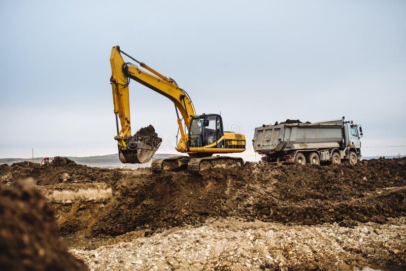 工业耐用挖掘机大厦高速公路机械、细节和装货在建造场所的倾销者卡车 免版税库存照片