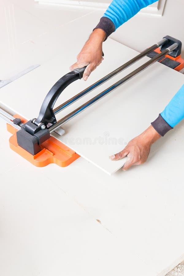 工业铺磁砖工建造者工作者与地垫切口设备一起使用 免版税库存照片