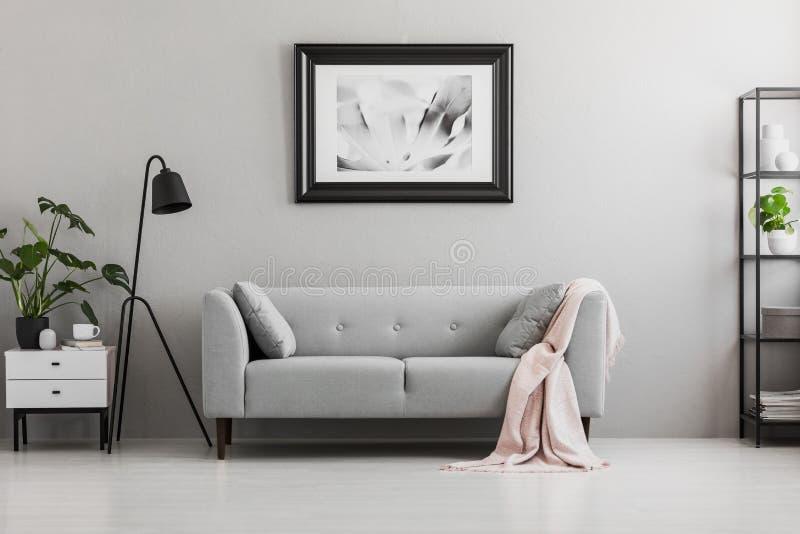 工业黑落地灯和一条桃红色毯子在典雅的长椅与坐垫在灰色客厅内部与地方a的 库存照片
